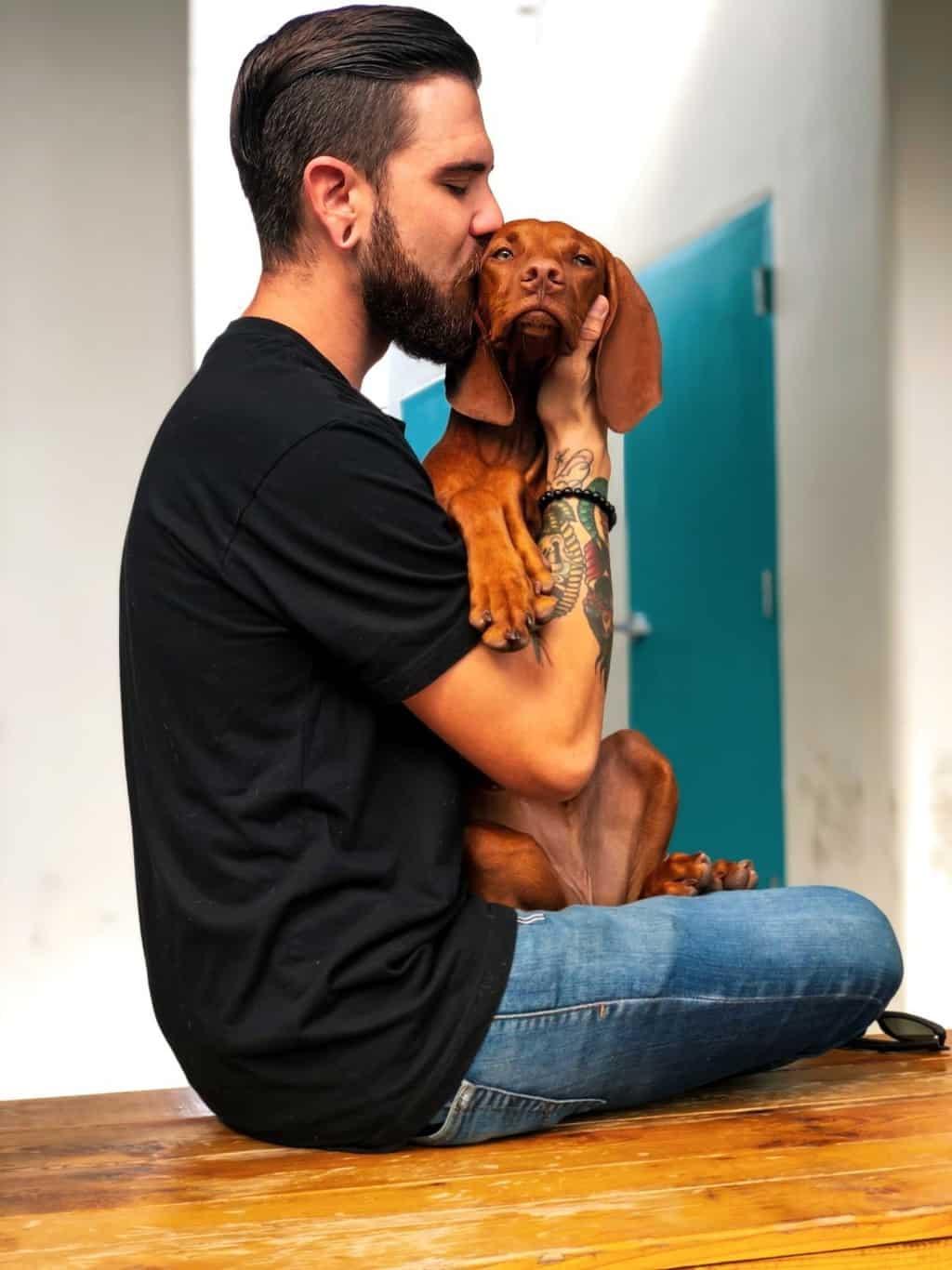 a man kissing his dog